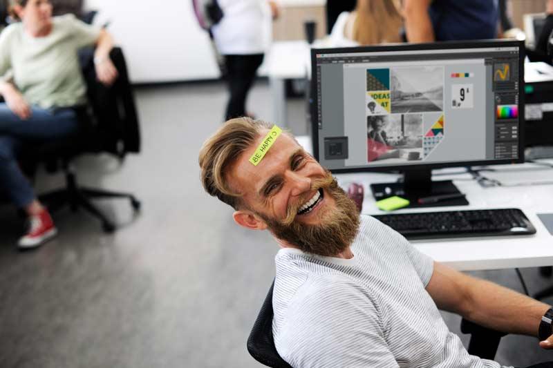 man lachend achter bureau met sticker op voorhoofd. PERIFACT factuur programma