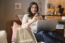 Dame zittend op bank met een laptop op de schoot