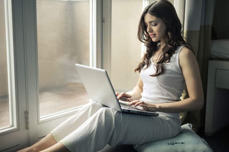 PERIFACT bestellen in de shop. Dame zittend op vensterbank met laptop op schoot