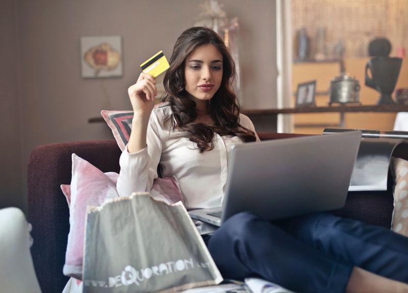 Vrouw achter laptop met pasje in haar hand